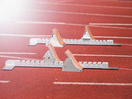 Starting blocks on red running tracks, light reflection an lens flare. Running training