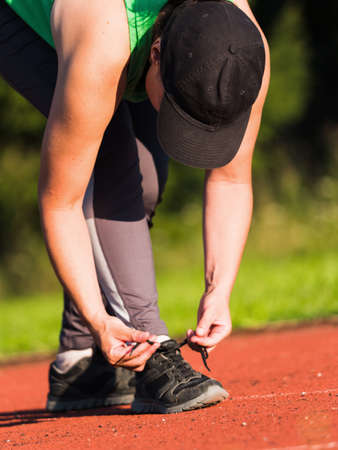 Middle age woman stopped to tie a string while running in the stadium. Black hair woman runner tying shoelace Imagens