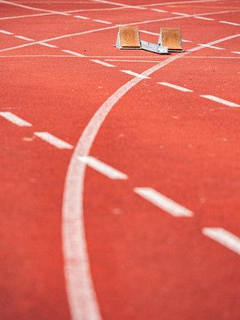 Empty starrting blocks at cindertrack of athletics stadium. Runner tracks painted on red tamrac