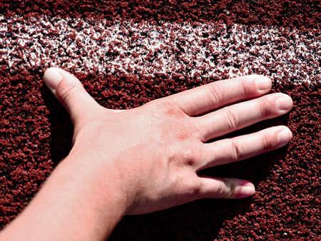 Runner in start position. Hands on starting line. Sport running in stadium.