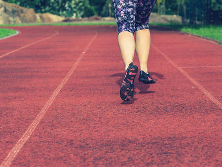 Mature asian woman in flowered leggings up her knees and toe shoes running along the stadium track.
