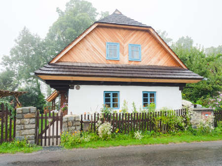 Lichnice village, Czechia. 26th of August 2021. Restored historic timbered cottage with a layer of clay on the peripheral wall, the so-called fur coat. Classic shingle roof.