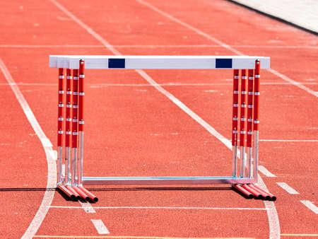 Hurdles and red running tracks in a stadium. Beginning of athletic training Imagens