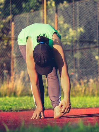 Preventive exercises against cramps and injuries of tendons and muscles. Sports woman stretching bare feet before run. Imagens