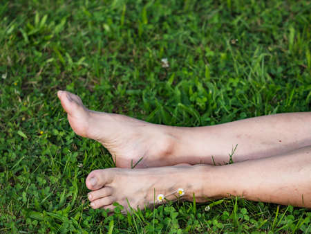 Tired female legs with bare feet on the green grass. Mature woman lays in short fresh green grass.