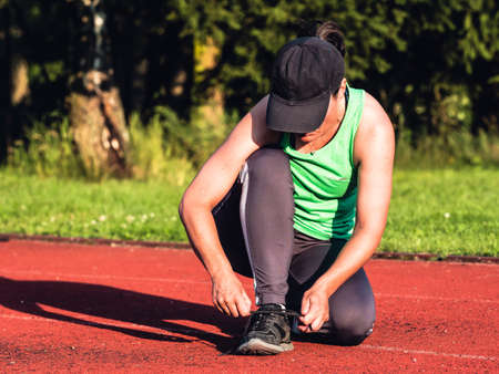 Female asian runner in green singlet stopped for lacing her sneakers. Health and sport concept