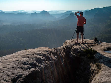 Man shadowing eyes at his big camera on tripod, taking photo of amazing day in hilly landscape