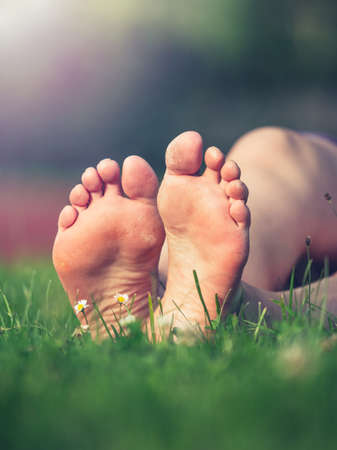 Dirty soles with hard dry skin of bare feet middle aged sporty woman. Female legs resting in fresh spring grass