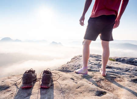 Middle age healthy male body with naked legs on mountain peak rock. Satisfy hiker enjoy view. Tall man on rocky cliff watching down to landscape. Imagens