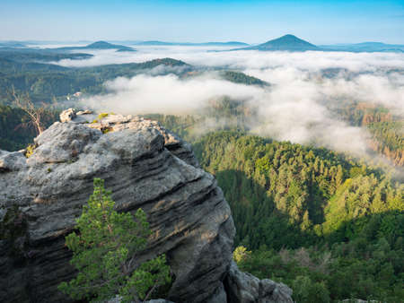 Morning view to misty Swiss Bohemian landscape during sunrise. Morning mist and fog over the valley near Jetrichovice village and forest in Bohemian Switzerland, Czech republic. Sandstone hills. Imagens