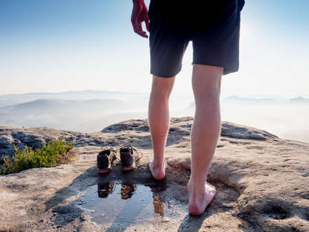 Hiker next to taken off shoes and water puddle on sandstone rock edge enjoy misty landscape view