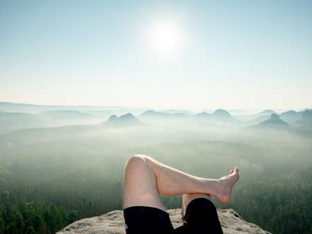 View above barefoot male body in black pants sleeping on cliff sticking out from morning fog. Natural park in Saxony, Germany Imagens