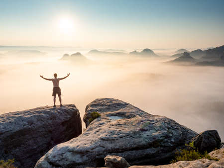 Silhouette of nature lover man with raised arms on the mountain sharp edge. Misty valley bellow man