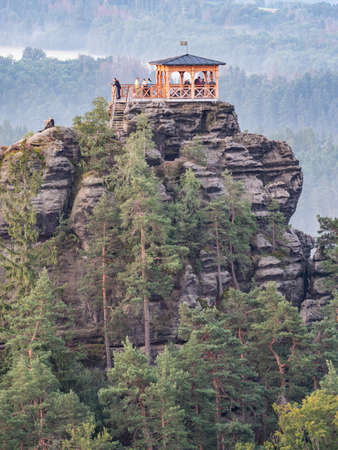 Breakfast or morning picnic of tourists group on popular lookout tower Mariina vyhlidka. The significant viewpoint in Bohemian Switzerland National Park, Czech Republic.