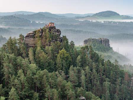 Breakfast during dawn in a restored gazebo on Marrina Rock. Misty morning panorama, Bohemia Switzerland National Park, Czech Republic. Imagens