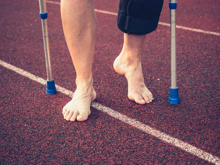 Hurts sports woman walks with knee brace after an injury by medical sticks. Tired barefoot mature woman. Imagens