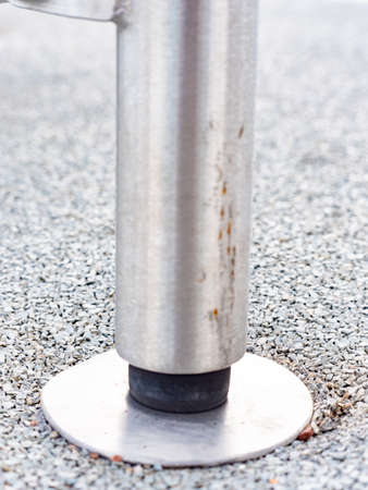 Construction base in soft rubbery tille. Chrome steel bar ends in safety ground of workout playground