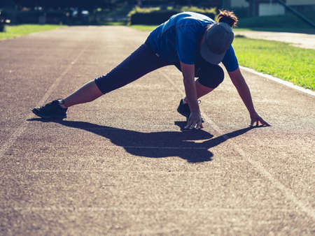 Sports woman stretching legs muscles and bend back before condition run on school stadium