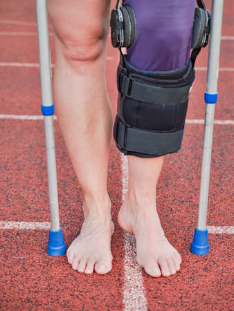 Woman suffering with walk by sticks and knee brace support surgery left knee in recovery time. Imagens
