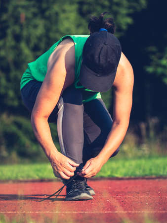 Young fit girl runner tying shoelaces. Athletic woman on red running stadium track Imagens