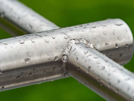 Rain drops on a gray metallic construction of chrome bars. Oudoor workout
