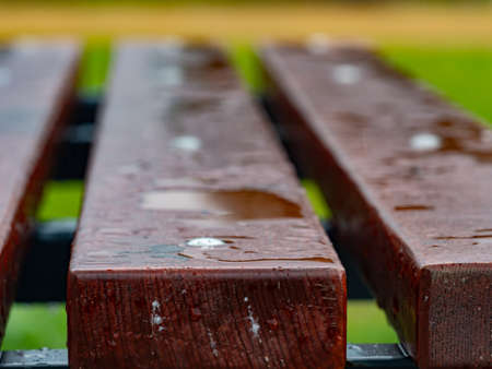 Water drops on a dark wooden background closeup. Oiled wooden planks surface resistant to water drops