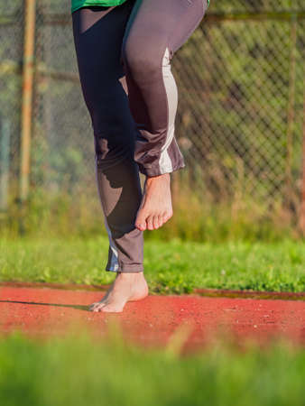 Middle age woman stretching knees and ankles, she jumping bare feet on red rubbery running track of outdoor stadium.