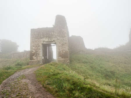 Main entrance into rest of ruin of stronghold Lichnice in heavy fog and cloudy rainy day. Czechia travel. Imagens