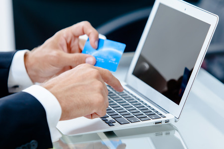 entering information: Closeup of a business man hands entering credit card information into a laptop  Stock Photo
