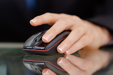 Closeup of a female s hand working on black computer mouse  Stock Photo - 26451343