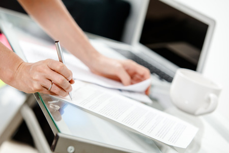 Close-up of secretary s hands doing paperwork  photo