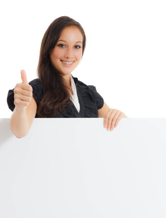 Portrait of a smiling young business woman holding at blank card in her hand  and showing thumb up sign against white background  photo