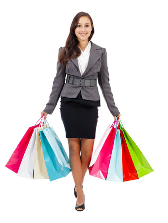 Portrait of stunning young woman carrying shopping bags against white background  Stock Photo - 26538985