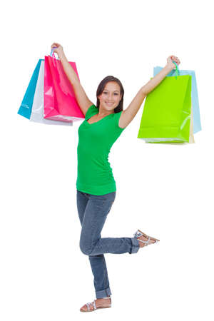 Portrait of stunning young woman carrying shopping bags against white background  Stock Photo - 26567683