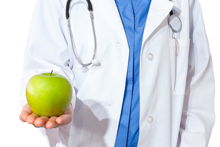 Smiling beautiful blond woman Doctor giving green apple, isolated over white  photo