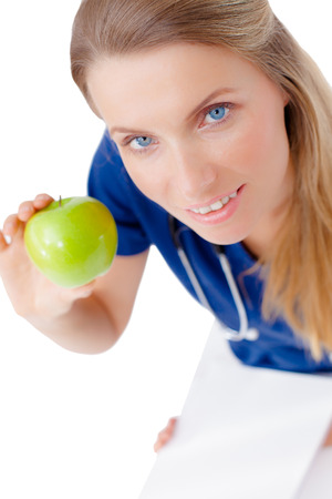 Smiling beautiful blond woman Doctor giving green apple, isolated over white background photo