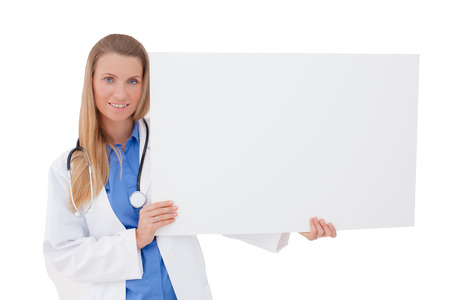 Portrait of a  smiling young Doctor holding a blank sheet of paper on white to write your text  Isolated on a white Copy space  photo