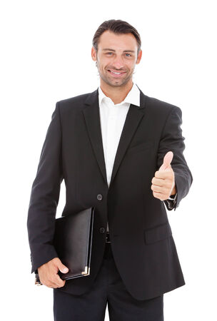 Portrait of young happy business man showing thumbs up sign  photo
