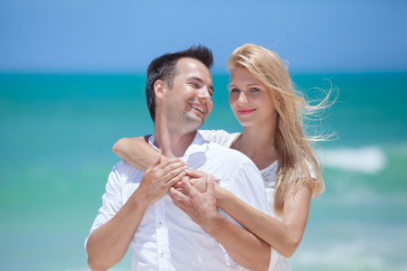 Smiling young couple embracing at beautiful summer beach