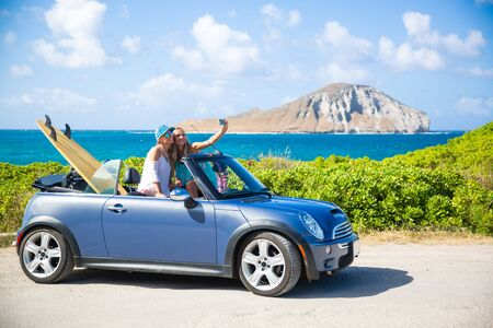 Car road trip vacation young people taking selfie photo with phone during summer travel vacation. Tourists couple taking photos on Hawaii in convertible car, with smartphone camera