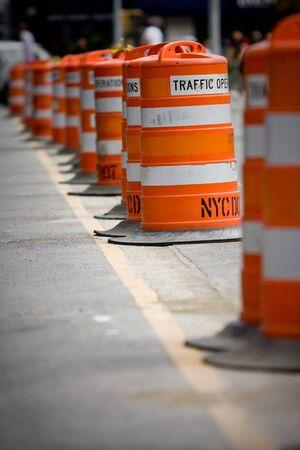 Orange traffic cones standing in a row on dark asphalt Stock Photo
