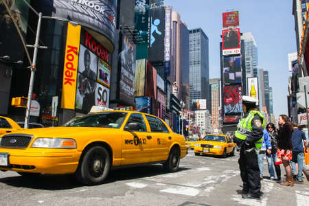 MANHATTAN, NY - February 20, 2011: Yellow Taxi on Broadway at Times Square in Manhattan, New York City with all the lit up billboards and advertisements.
