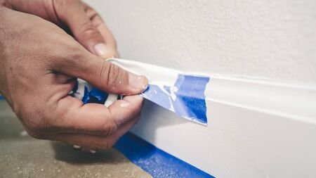 Removing masking tape from molding. A painter pulls of blue painter's tape from the wall to reveal a clean edge baseboard.