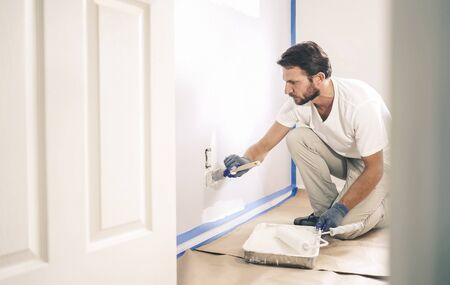 Close up of painter man with gloves painting the wall around power outlet.