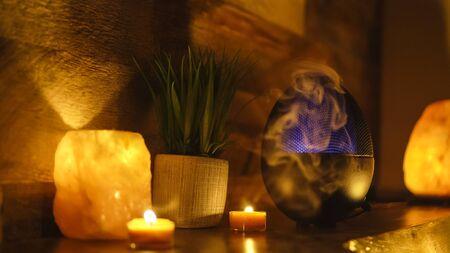 Aroma electric oil diffuser lamp, candles on wooden table in room. Aromatherapy.
