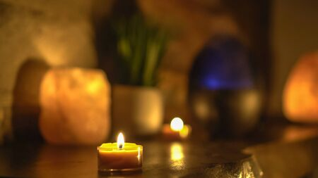 Close-up of burning tealight candle on table in home. Romantic atmosphere with scented aroma tea light candles.