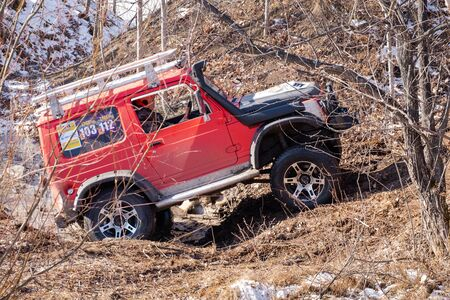 Khabarovsk, Russia - Nov 11, 2019: Jeep Suzuki Jimny overcomes obstacles in the forest.