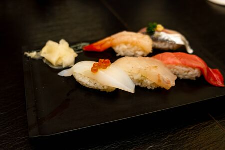Real Japanese sushi in a restaurant in Tokyo. Set of sushi on a black plate made of stone
