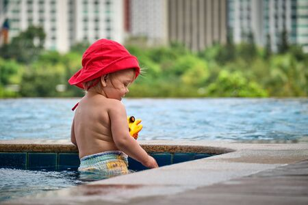 Little girl in the pool on the roof of the hotel. View of the city of Manila from the pool of the luxury five-star hotel. Sunny weather. Skyscrapers on the background.