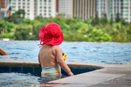 Little girl in the pool on the roof of the hotel. View of the city of Manila from the pool of the luxury five-star Discovery Primea hotel. Sunny weather. Skyscrapers on the background. Stock Photo